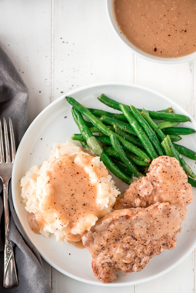 These super tender Slow Cooker Pork Chops and Gravy take just 10 minutes to prep! In four hours you'll be sitting down to a delicious home cooked meal.