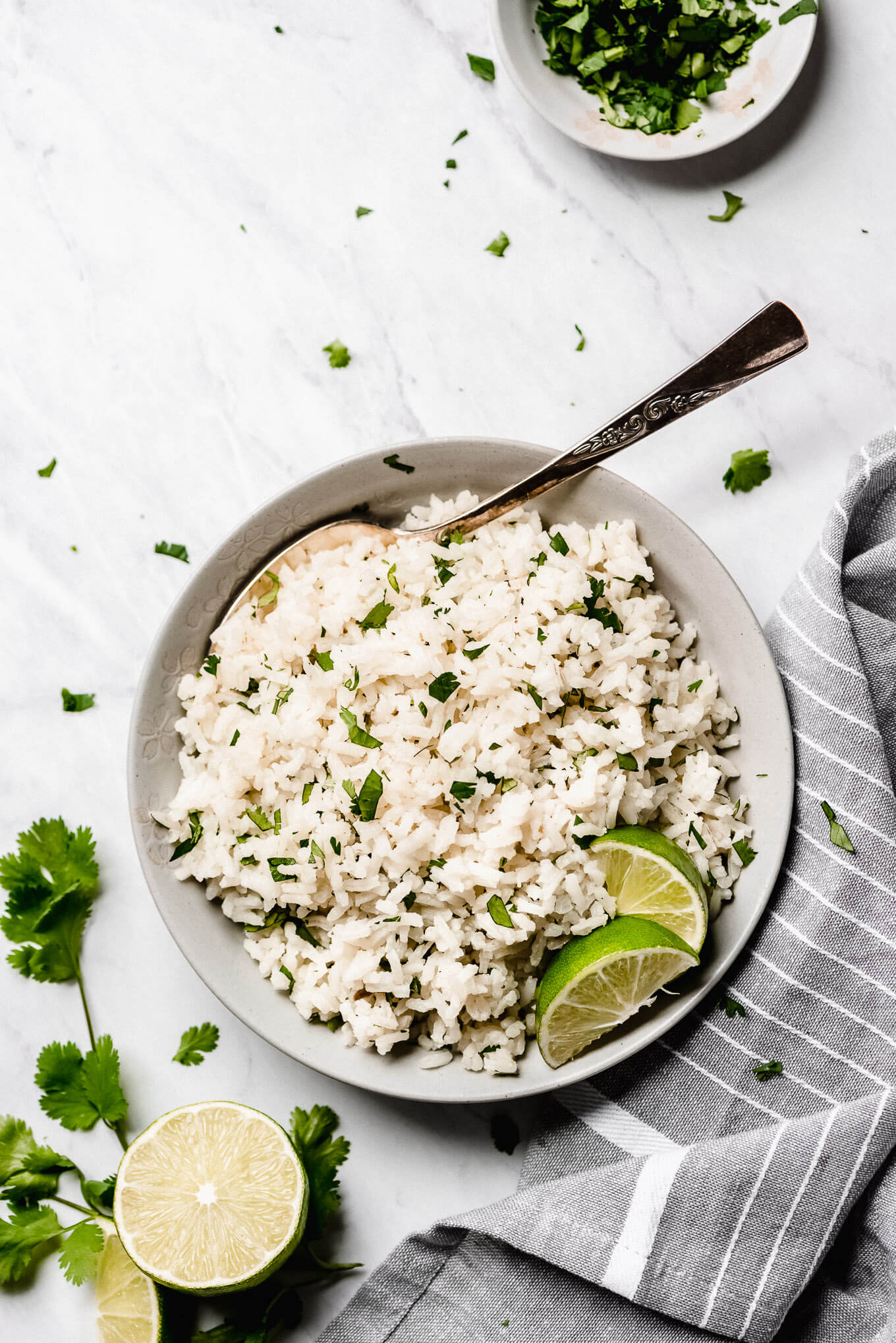 Top view of Cilantro Lime Rice in a serving bowl garnished with lime wedges and a bowl of chopped cilantro to the side.