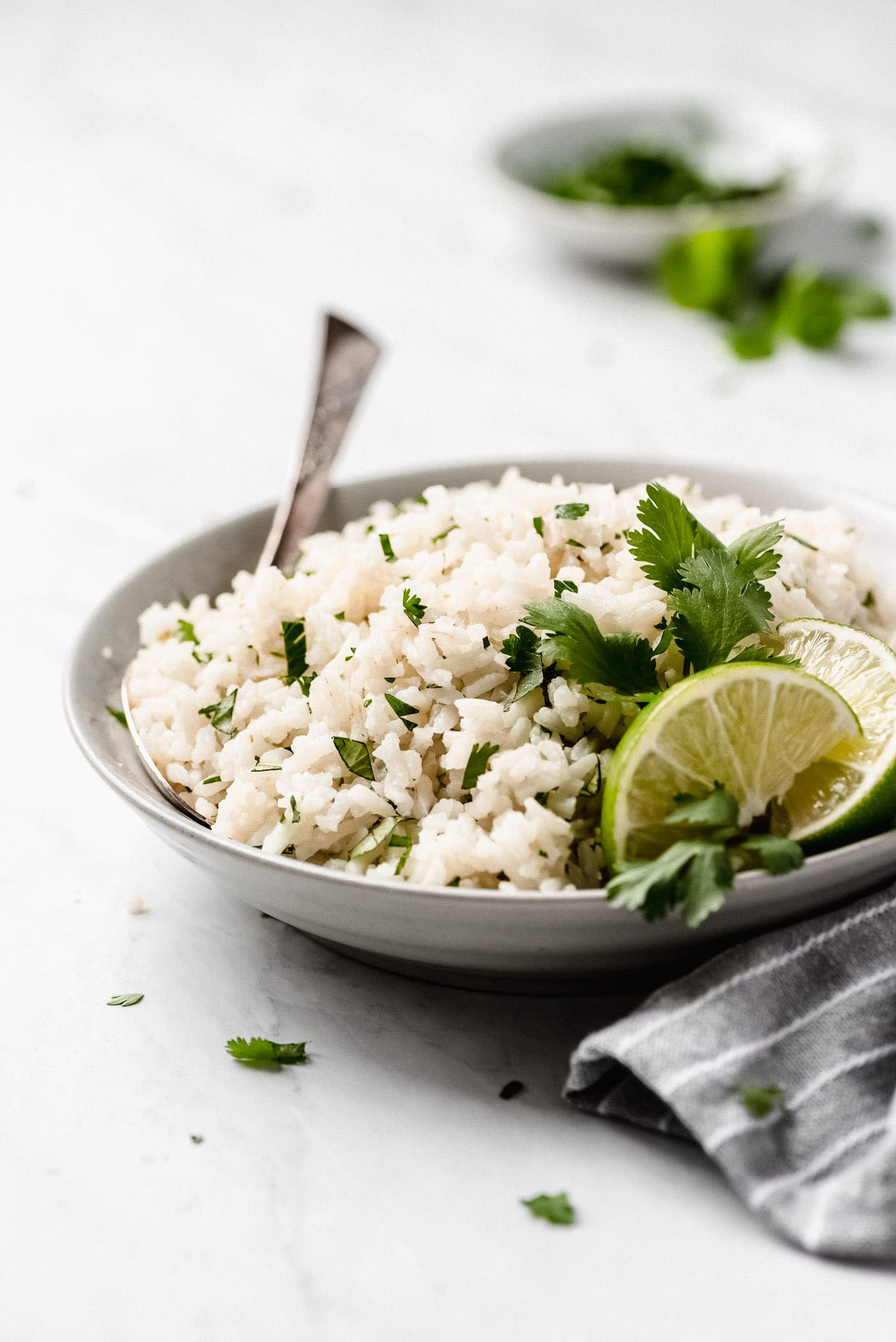 Cilantro Lime Rice like Chioptle's in a bowl garnished with lime wedges and cilantro leaves.