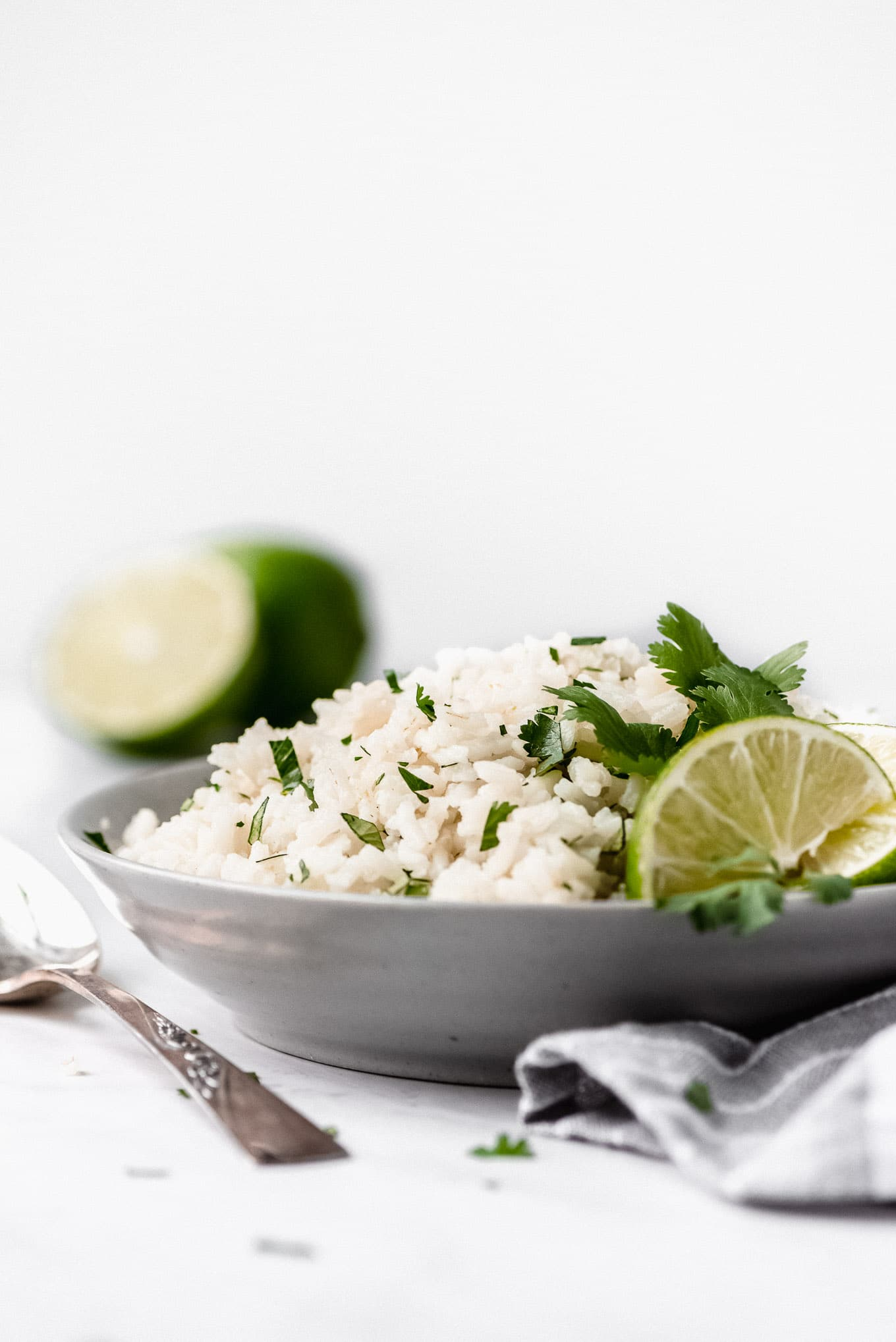 Side view of Cilantro Lime Rice piled high in a bowl and garnished with lime edges and cilantro leaves.