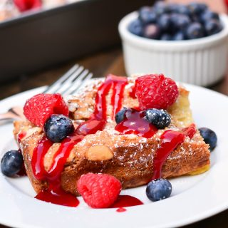 French toast casserole baked with a coconut almond puree and served with fresh berries and raspberry sauce