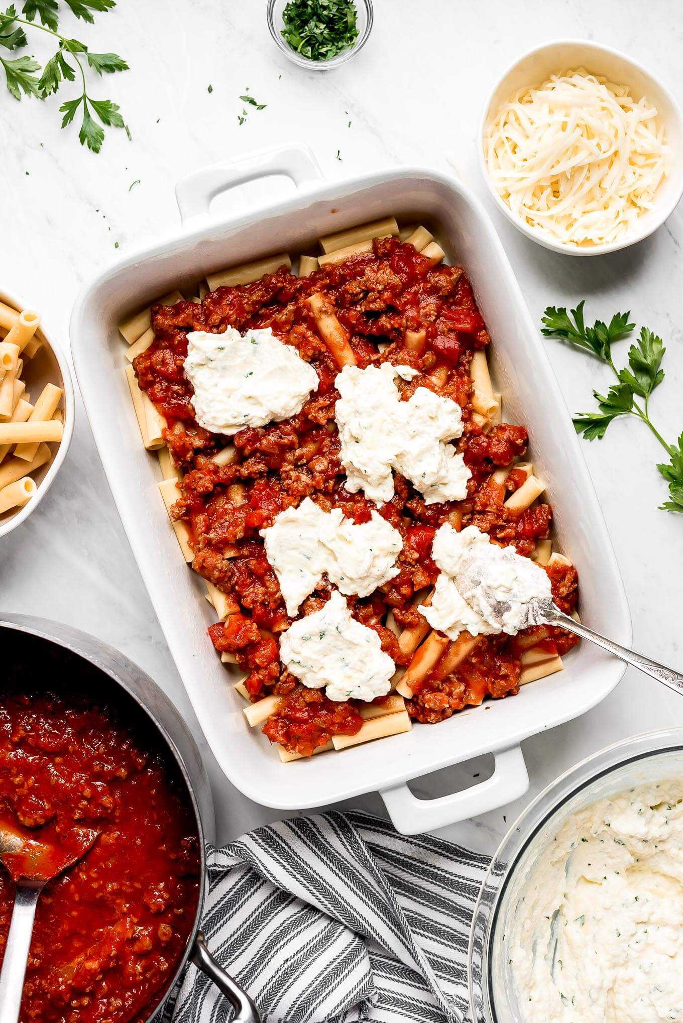 Assembling baked ziti in a casserole dish with a layer of ziti pasta, sausage tomato sauce, and dots of ricotta cheese mixture.