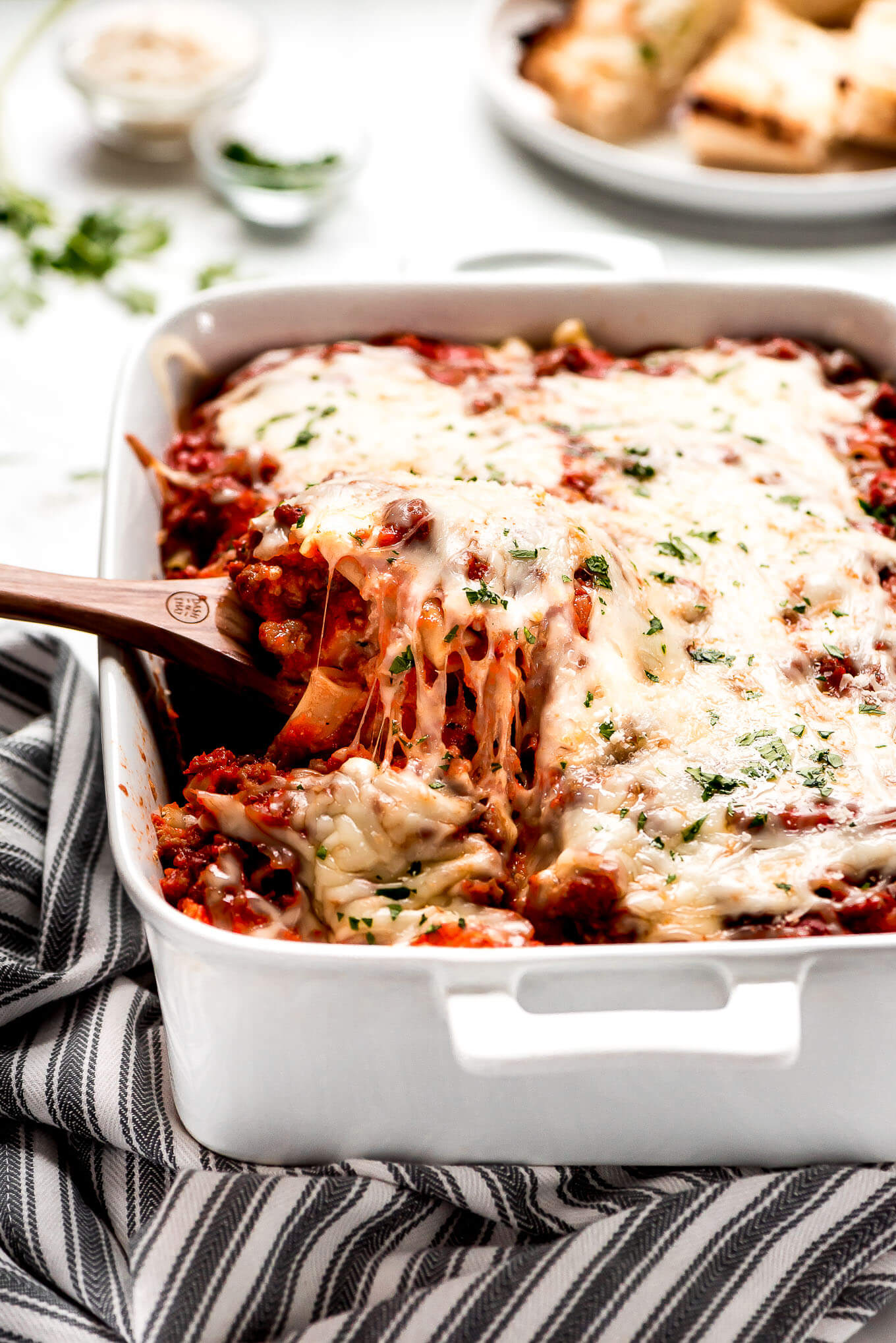 Lifting a large spoonful of baked ziti from a white baking dish.
