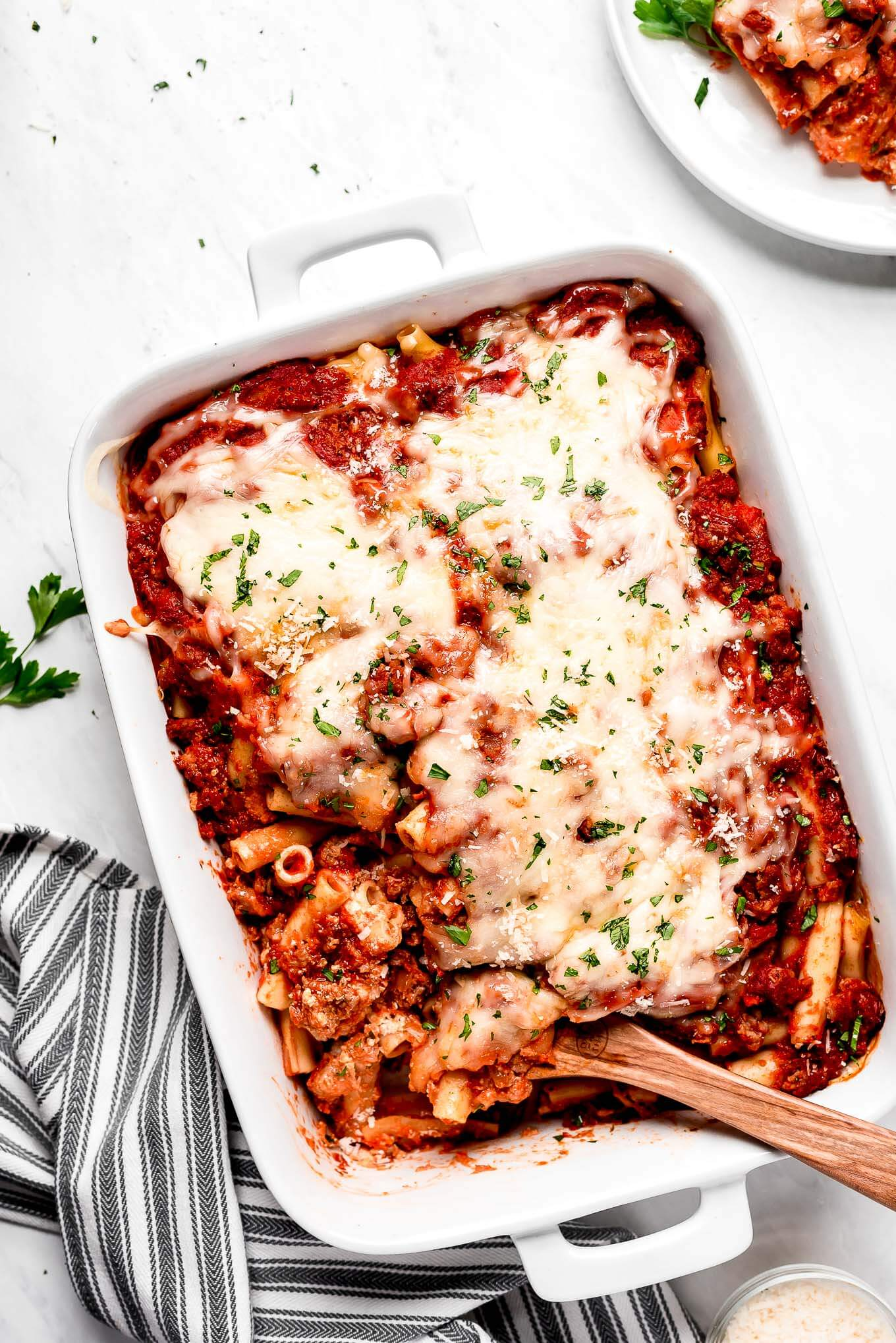 A white casserole dish of Baked Ziti with Sweet Italian Sausage with a wooden spoon in it.