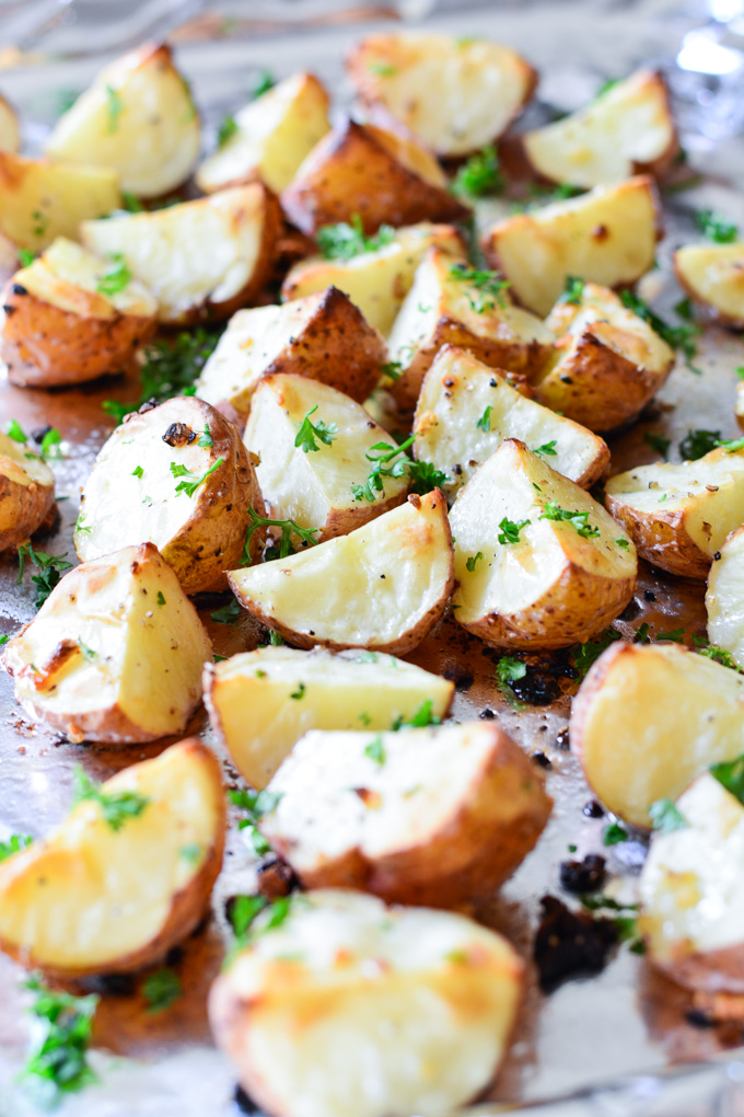 Garlic Roasted Red Potatoes on a baking sheet sprinkled with fresh parsley.