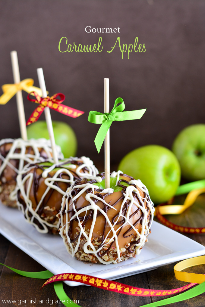 Caramel Apples drizzled with chocolate and dipped in nuts, sitting on plate and ribbons and green apples scattered around on the table.
