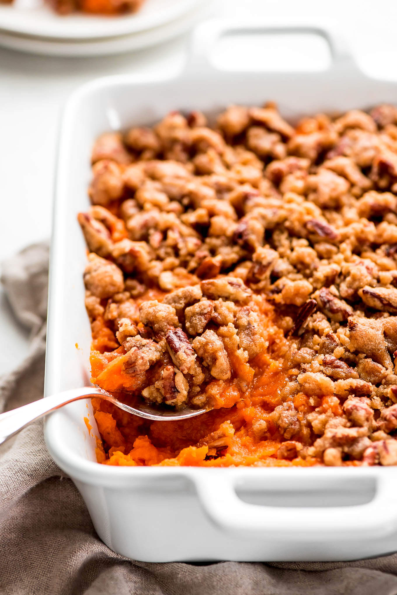 A spoon scooping out sweet potatoes out of a casserole dish.