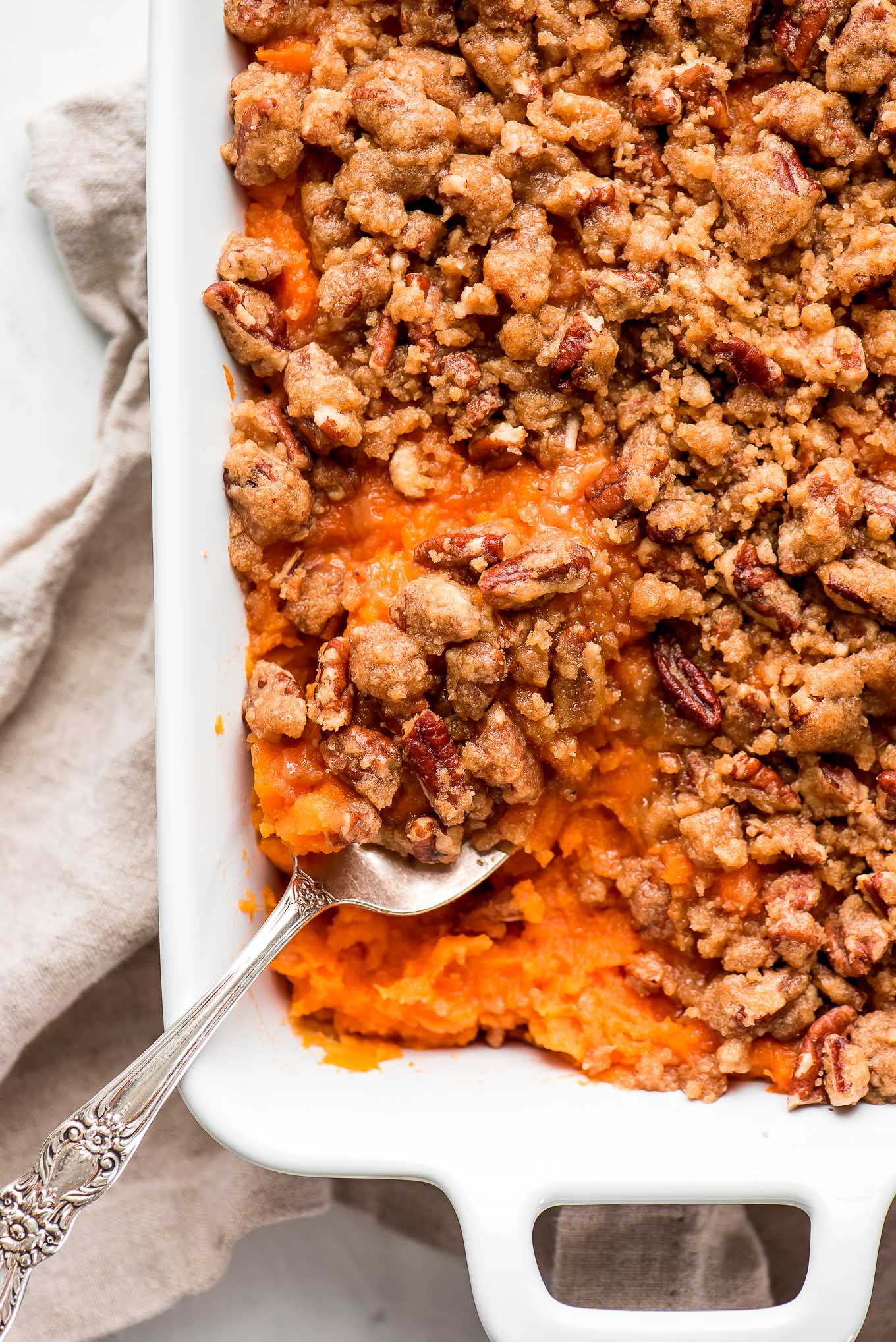 Close up of Sweet Potato Casserole with a spoon in the dish.