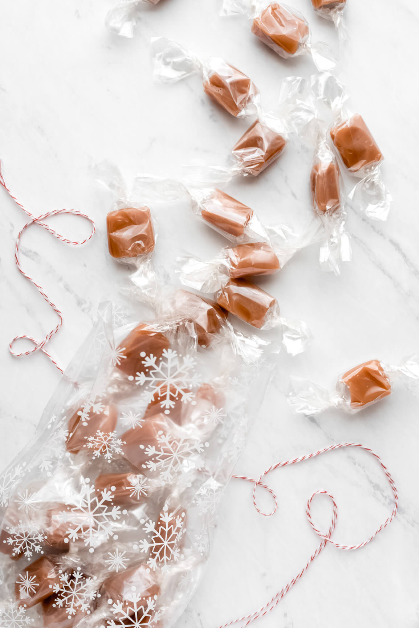 Homemade caramel wrapped in cellophane and spilling out of a cellophane bag onto a marble surface.