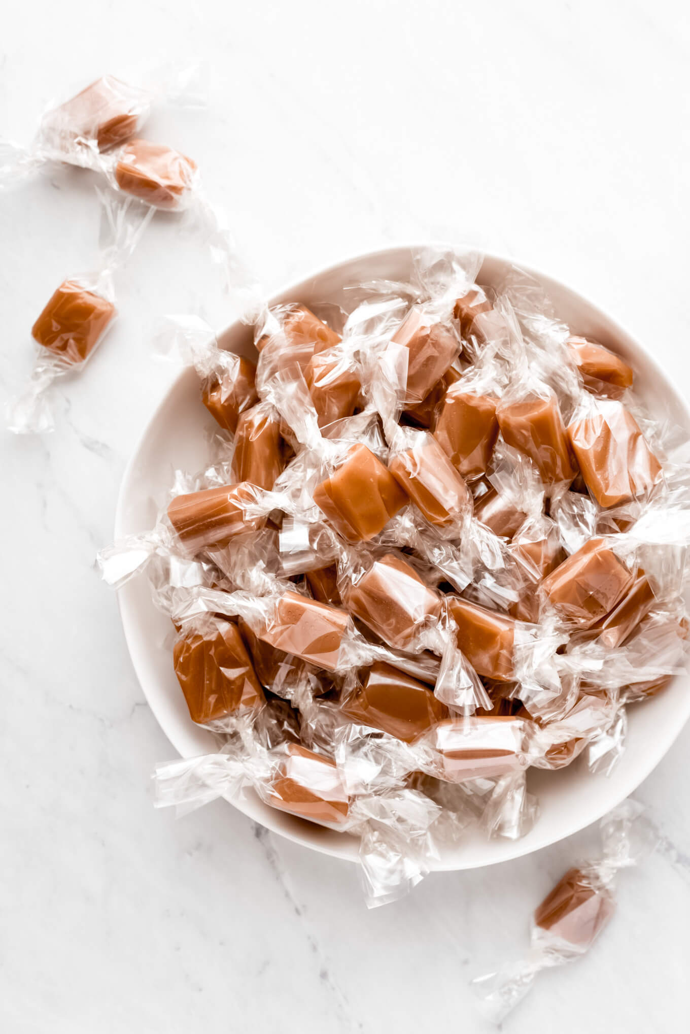 Homemade Caramels wrapped in cellophane and in a bowl.