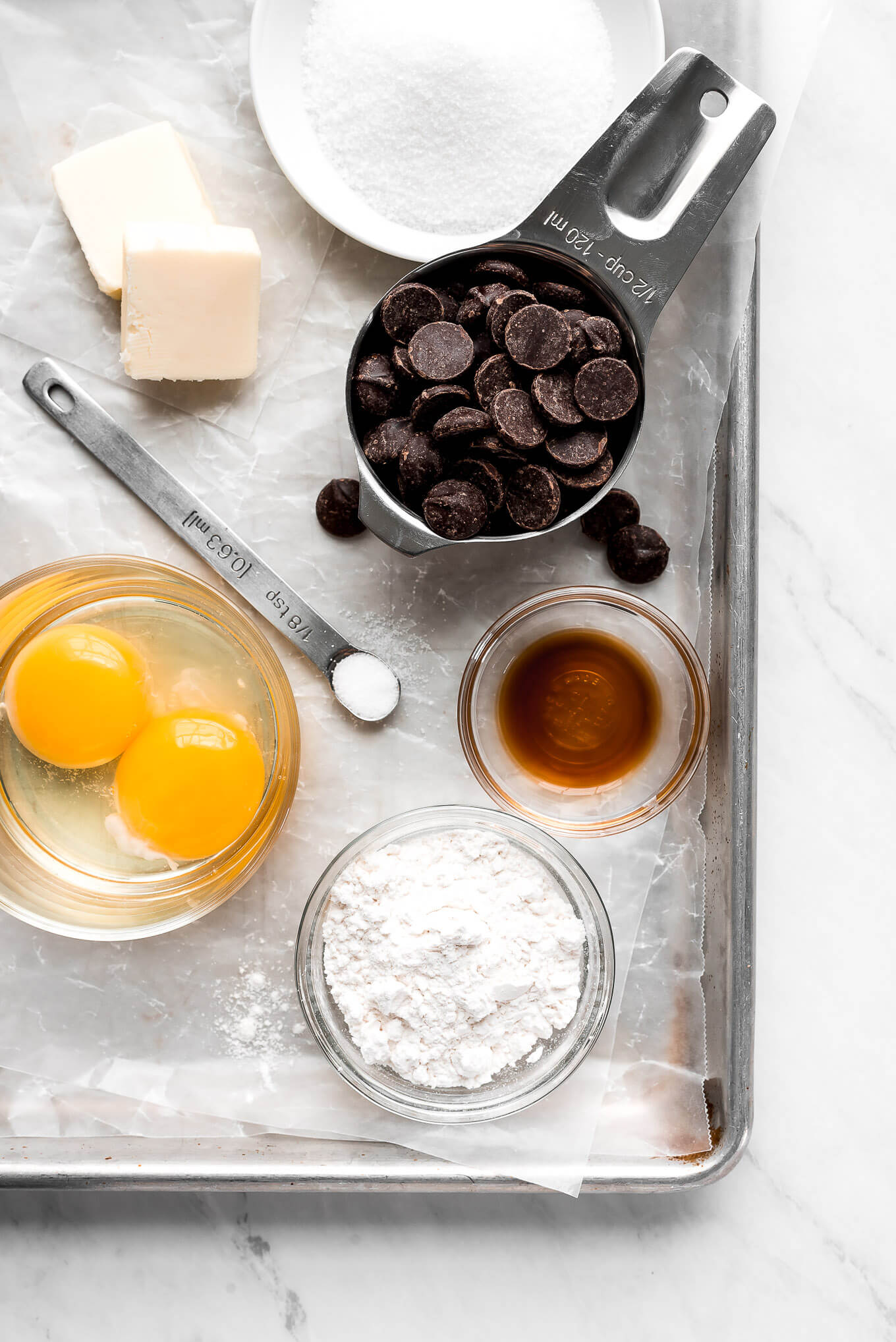 A baking sheet with ingredients on it- chocolate chips, sugar, butter, vanilla extract, salt, eggs, and flour.