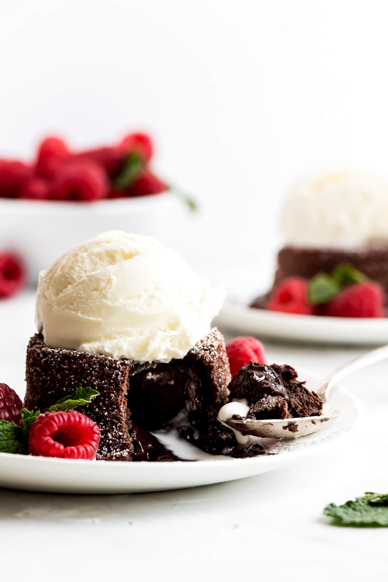 Chocolate Lava Cake on a plate with raspberries and a scoop of vanilla ice cream on top.