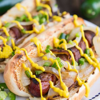 Hot dogs wrapped in bacon and topped with grilled onions, jalapenos, and Heinz Mustard