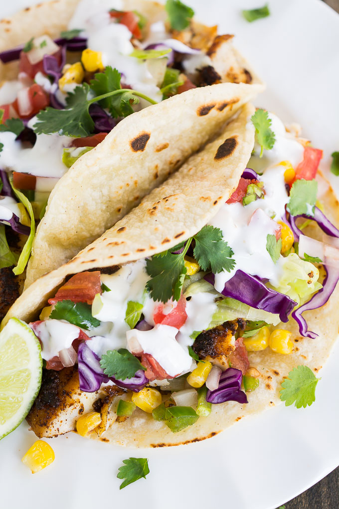 Tacos filled with spicy pan-seared tilapia, cabbage, lettuce, corn, and pico de gallo.