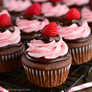 Rich chocolate cupcakes topped with chocolate ganache and raspberry cream cheese frosting