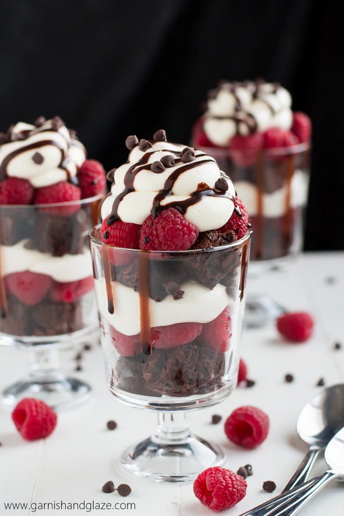 Side shot of mini Raspberry Brownie Cheesecake Trifles showing layers of brownie, raspberries, cheesecake and drizzles with chocolate and chocolate chips.