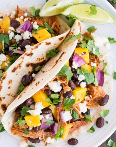 Easy slow-cooker Chipotle Pork Tacos with mango salsa on top are the perfect summer blend of sweet and spicy!