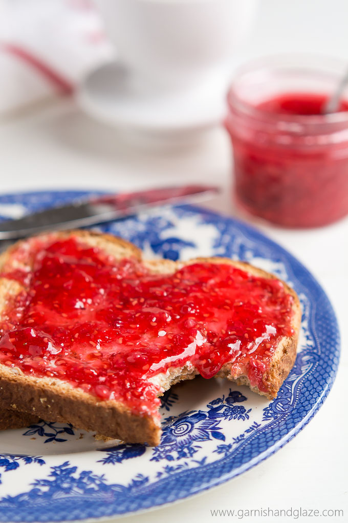 Raspberry Freezer Jam spread over toast that is on a plate.