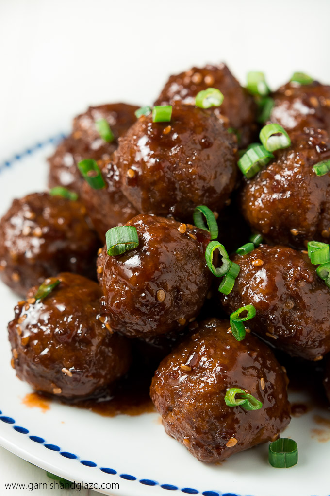 beef appetizers on a plate with green onions sprinkled on top