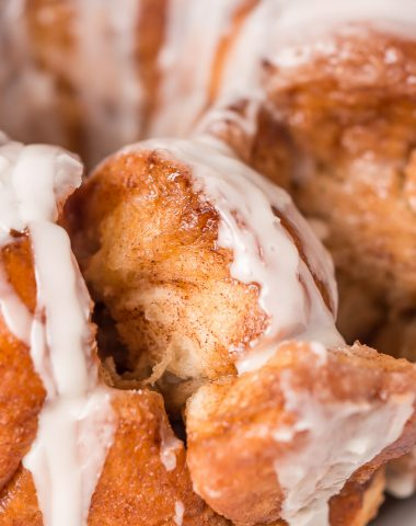 Gather round the table with your family for some Glazed Monkey Bread-- irresistible fluffy, buttery, cinnamon and sugar coated balls of bread, covered in a creamy glaze.