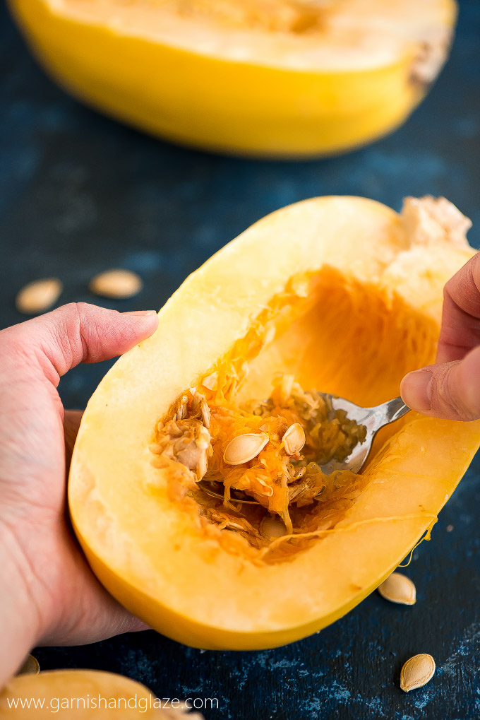 Scooping seeds out of half of a spaghetti squash.