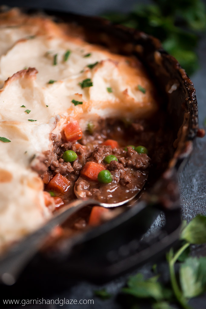 Close up view of the saucy ground beef and vegetable filling of Cottage Pie topped with browned mashed potatoes.