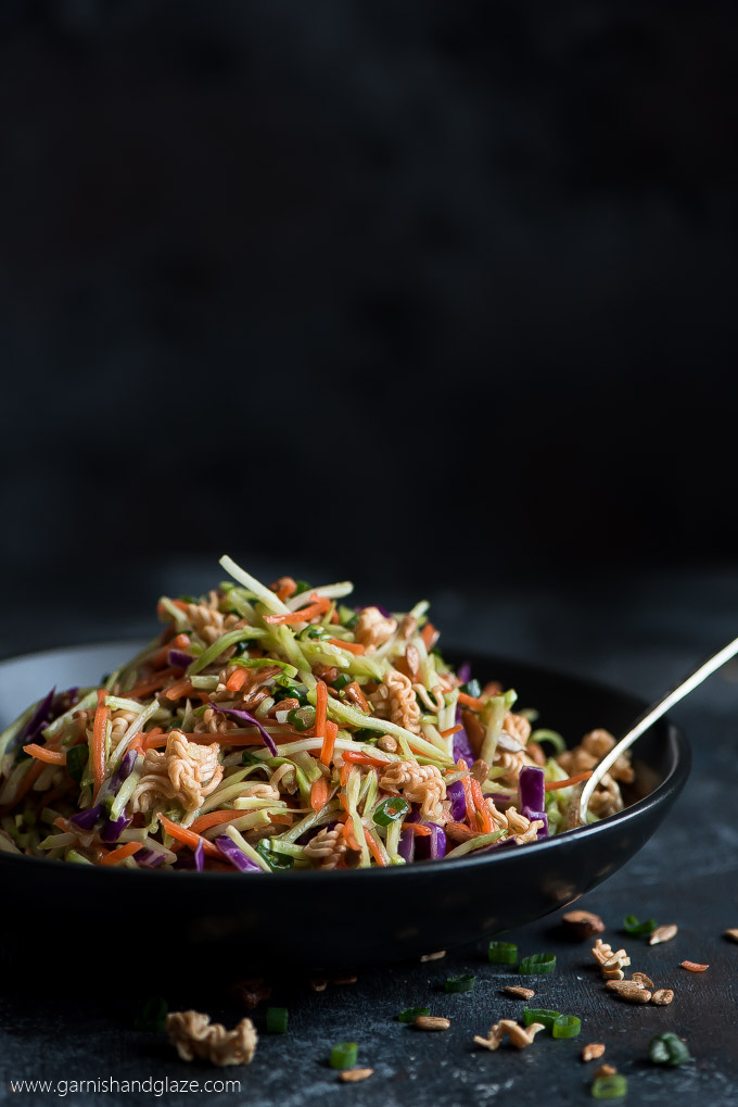 Crunchy Asian Broccoli Slaw Salad piled high in a black bowl and a spoon in the side.