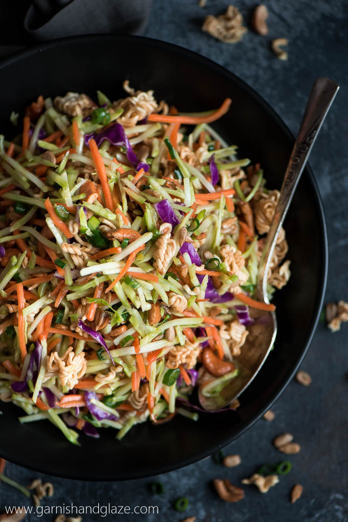 Flat lay of a bowl of Crunchy Asian Broccoli Slaw salad filled with carrots, cabbage, broccoli, cashews, and toasted ramen noodles.