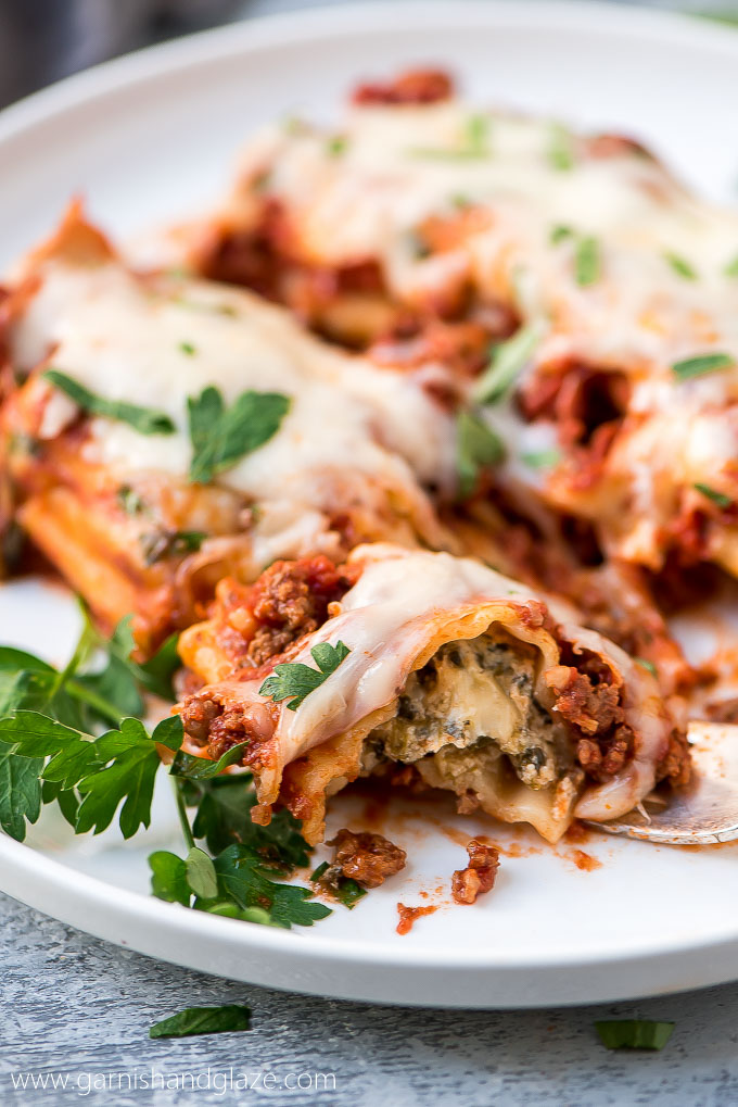 A close up shot of manicotti stuffed with spinach and cheese.