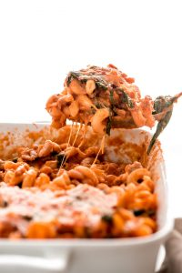 Spoonful of White Bean Sausage Pumpkin Pasta Bake from pan with strings of melted cheese