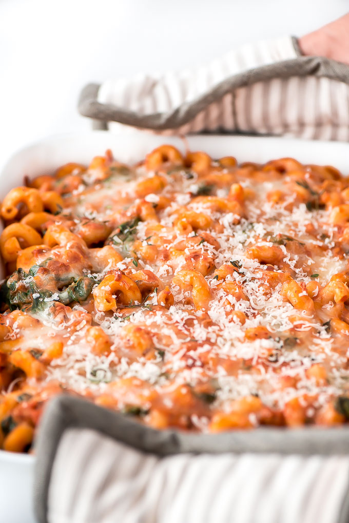 Holding pan of White Bean, Sausage, Pumpkin Pasta Bake with hot pads