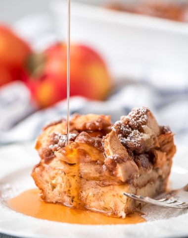 One plate square slice of Overnight Apple French Toast Casserole topped with powdered sugar and maple syrup being drizzled over the top.