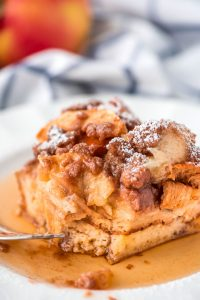 One plate square slice of Overnight Apple French Toast Casserole topped with powdered sugar and maple syrup.