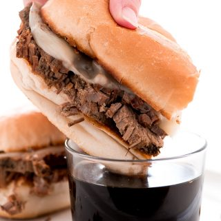 Dinner just got better with these Slow Cooker French Dip Sandwiches with hearty beef and melted provolone cheese on a toasted bun and dipped in au jus.