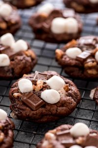 Rocky Road Cookies on cooling rack. Chocolate cookies loaded with marshmallows, chocolate chunks, and walnuts.