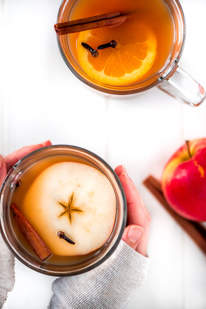 Two glass mugs of slow cooker wassail with an apple slice, orange, slice, cloves, and cinnamon stick floating on top. Hands are wrapped around one of the mugs.