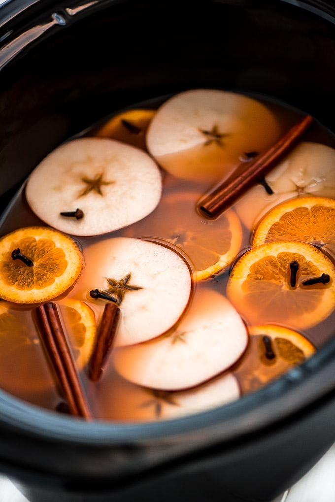 Slow Cooker Wassail in the slow cooker with lots of apple slices, orange slices, cinnamon sticks, and cloves floating in it.