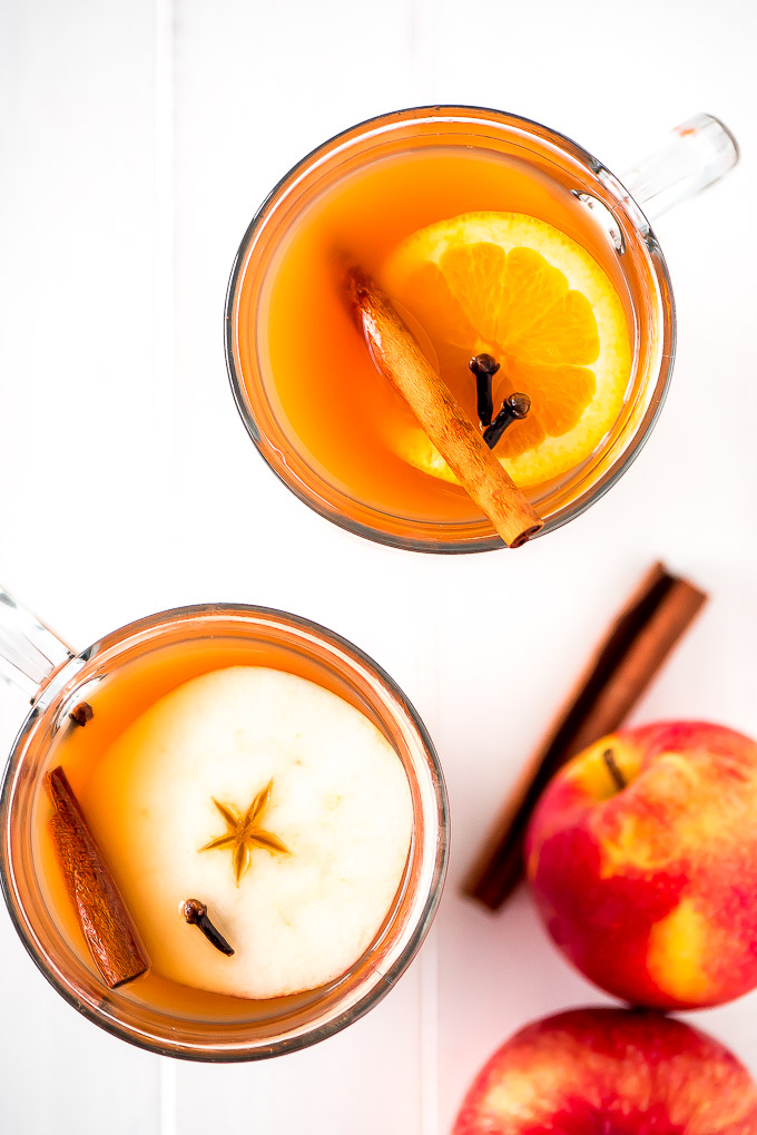 Glass mugs of slow cooker wassail with an apple slice, orange, slice, cloves, and cinnamon stick floating on top.