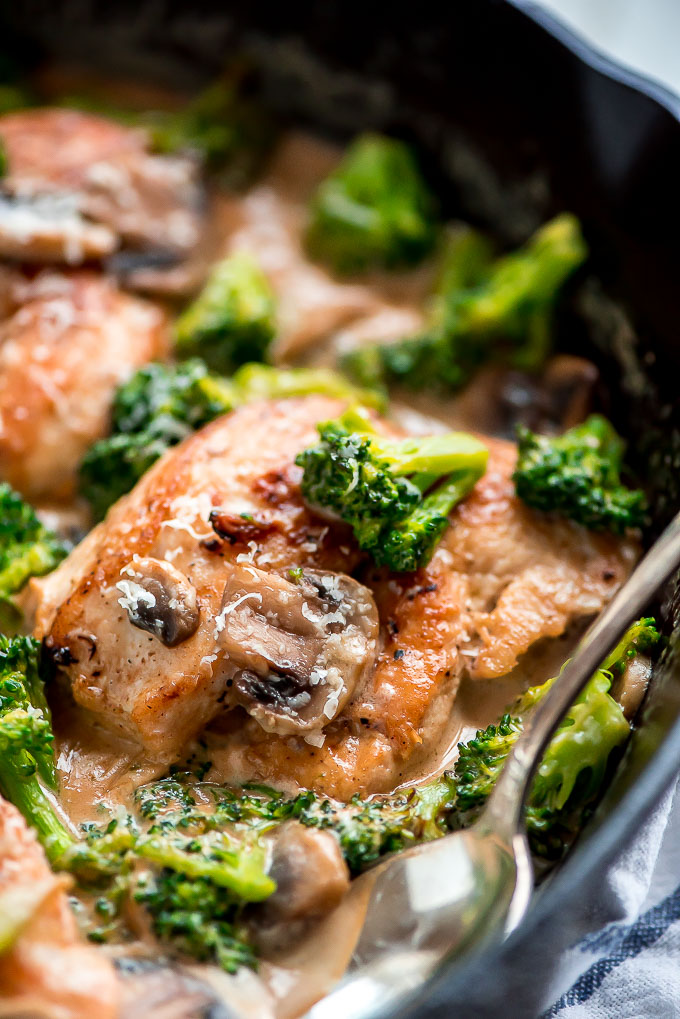 Cast iron skillet with One Skillet Chicken and Broccoli in it, covered in a garlic mushroom cream sauce.