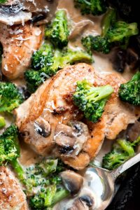 Close up birds eye view of a skillet of cooked chicken and broccoli.