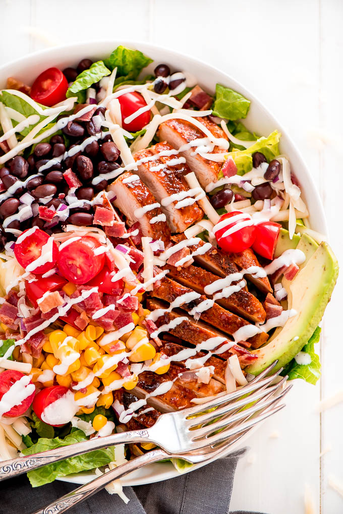 BBQ Chicken Salad loaded with avocado, black beans, tomatoes, bacon, corn, cheese, and chicken on a bed of chopped Romaine lettuce, and drizzled with ranch dressing.