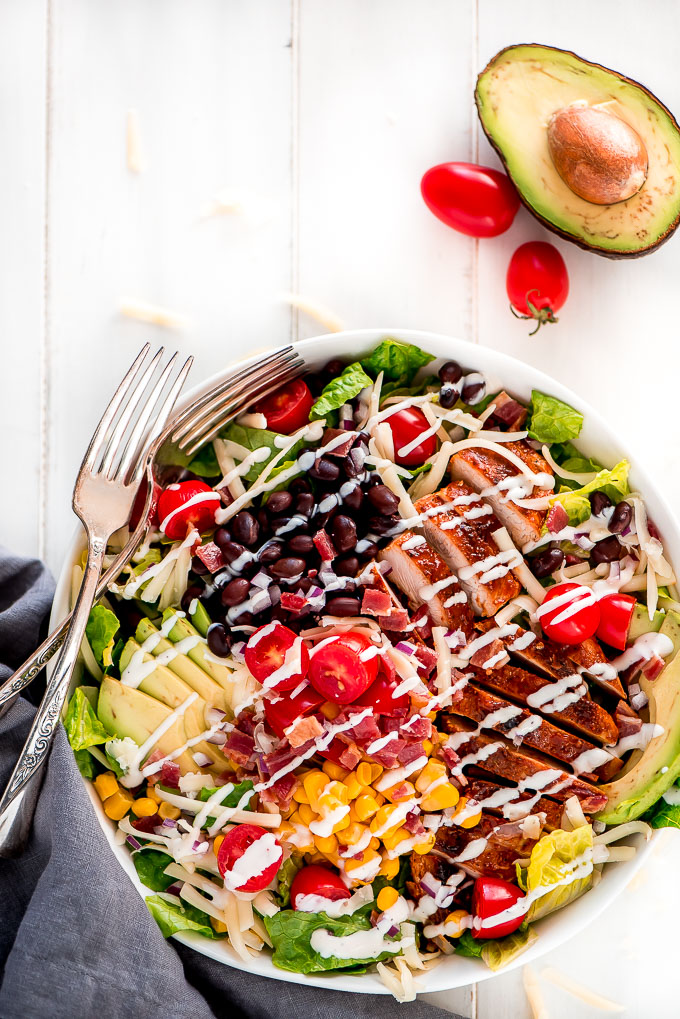 BBQ Chicken Salad loaded with avocado, black beans, tomatoes, bacon, corn, cheese, and chicken on a bed of chopped Romaine lettuce.