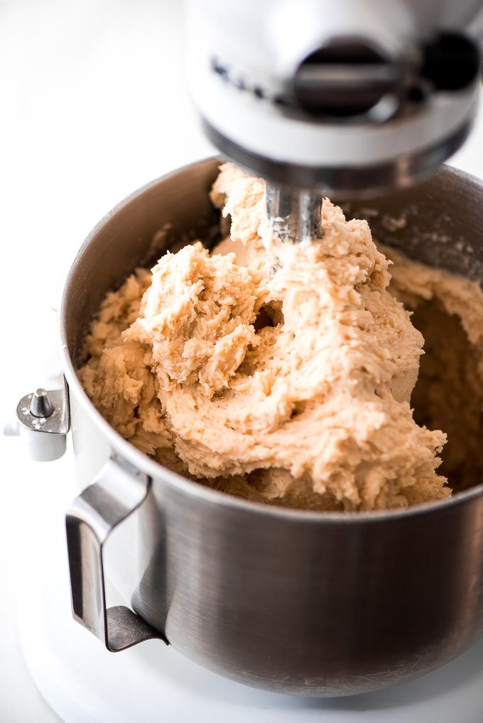 Sugar cookie dough in a KitchenAid mixer.