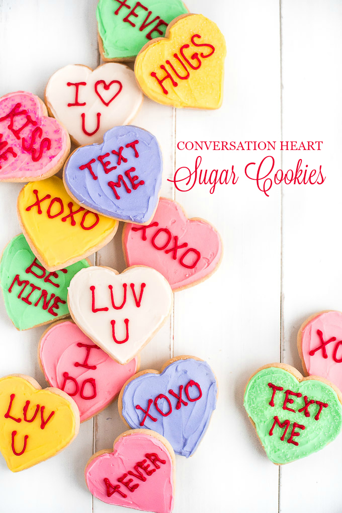 Table full of Conversation Heart Sugar Cookies with Valentine's Day messages written on top of each.