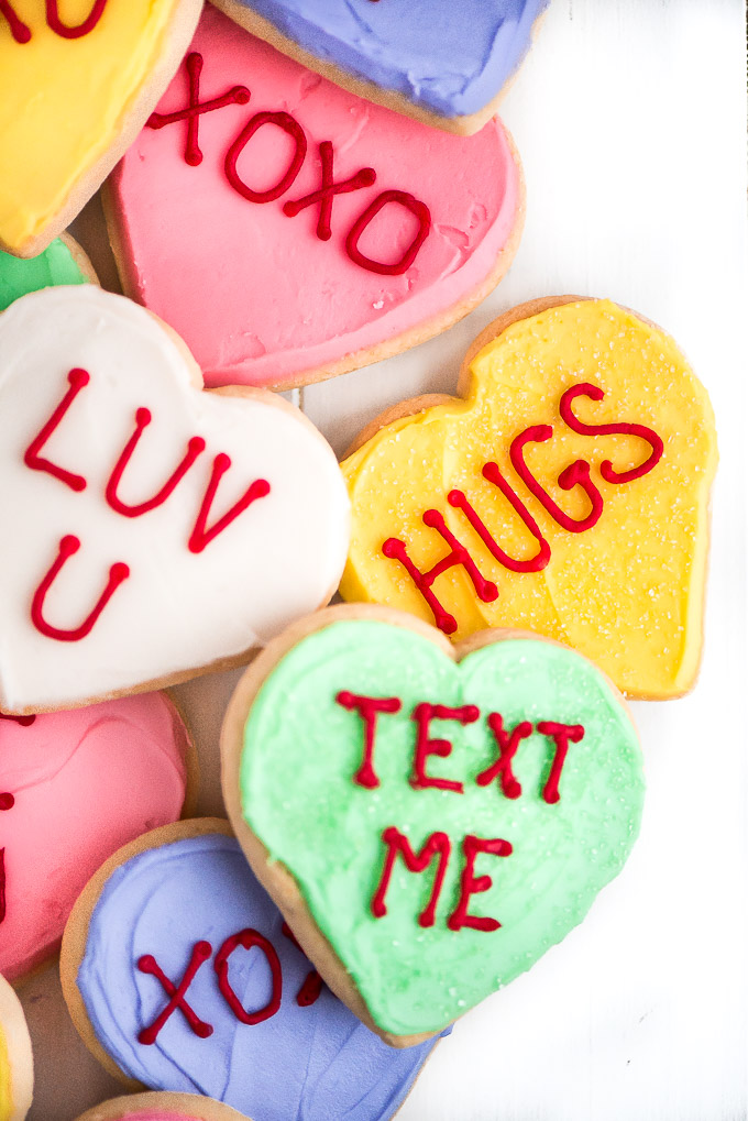 "Up close shot of conversation heart sugar cookies with messages ""HUGS"", ""XOXO"", ""LUV U"", and ""TEXT ME""."