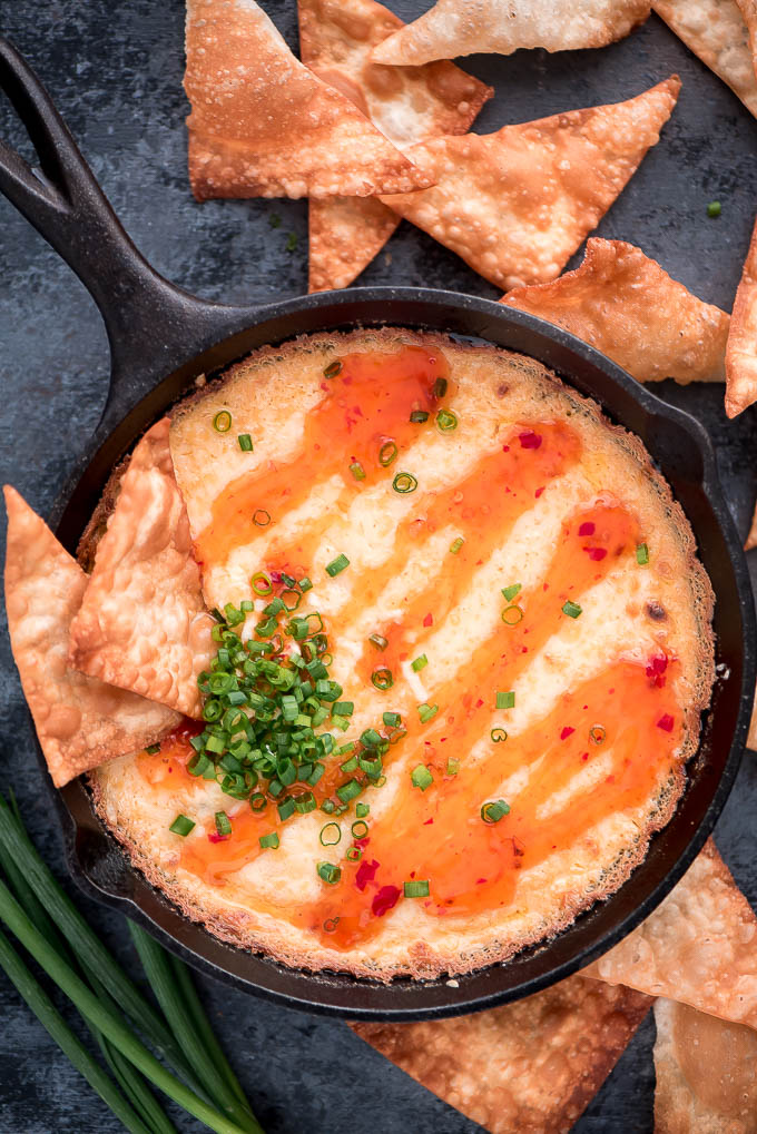 Cast iron skillet of Crab Rangoon Dip with wonton chips around it on the table.