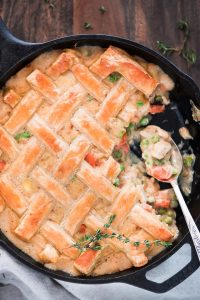 Easy Chicken Pot Pie in a skillet scooped into, showing the chicken, carrot, and pea filling.