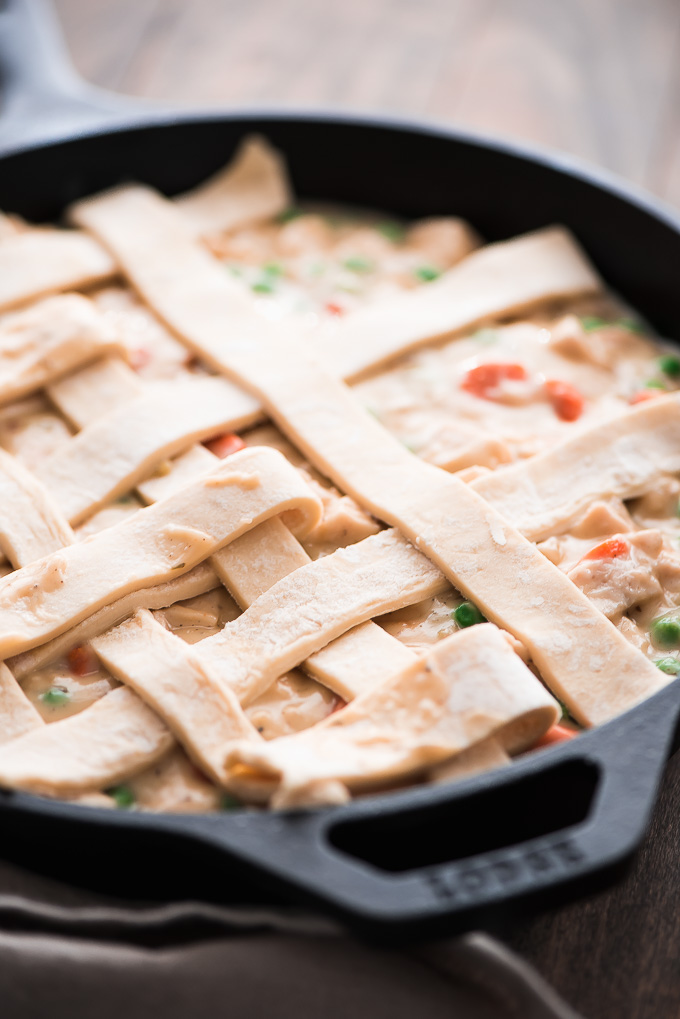 Chicken Pot Pie filling in a skillet with puff pastry dough strips on top forming a lattice.