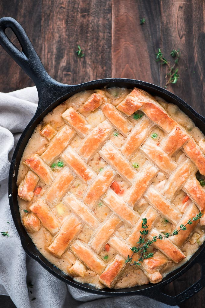 Cooked skillet chicken pot pie with a golden puff pastry lattice top.