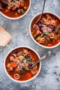 Multiple bowls of Minestrone Soup sprinkled with Parmesan cheese.
